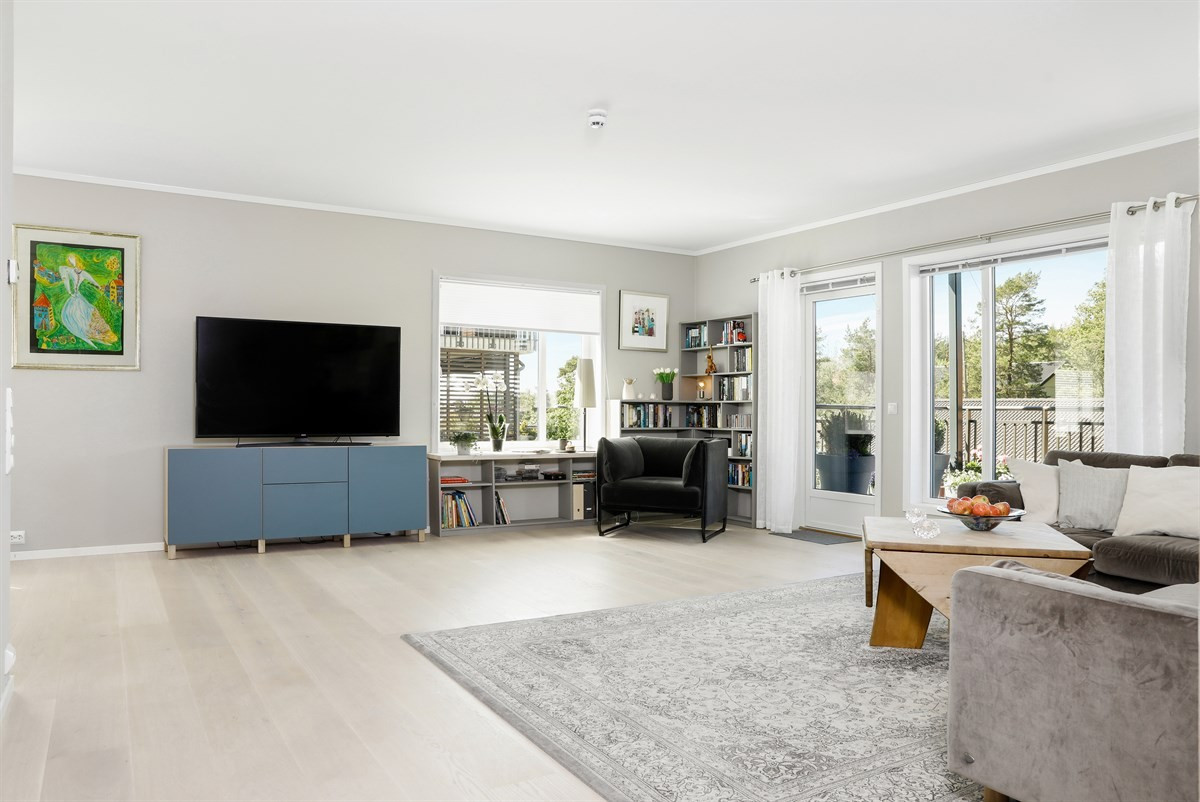 Stor lys stue med god plass til møblering i ulike soner