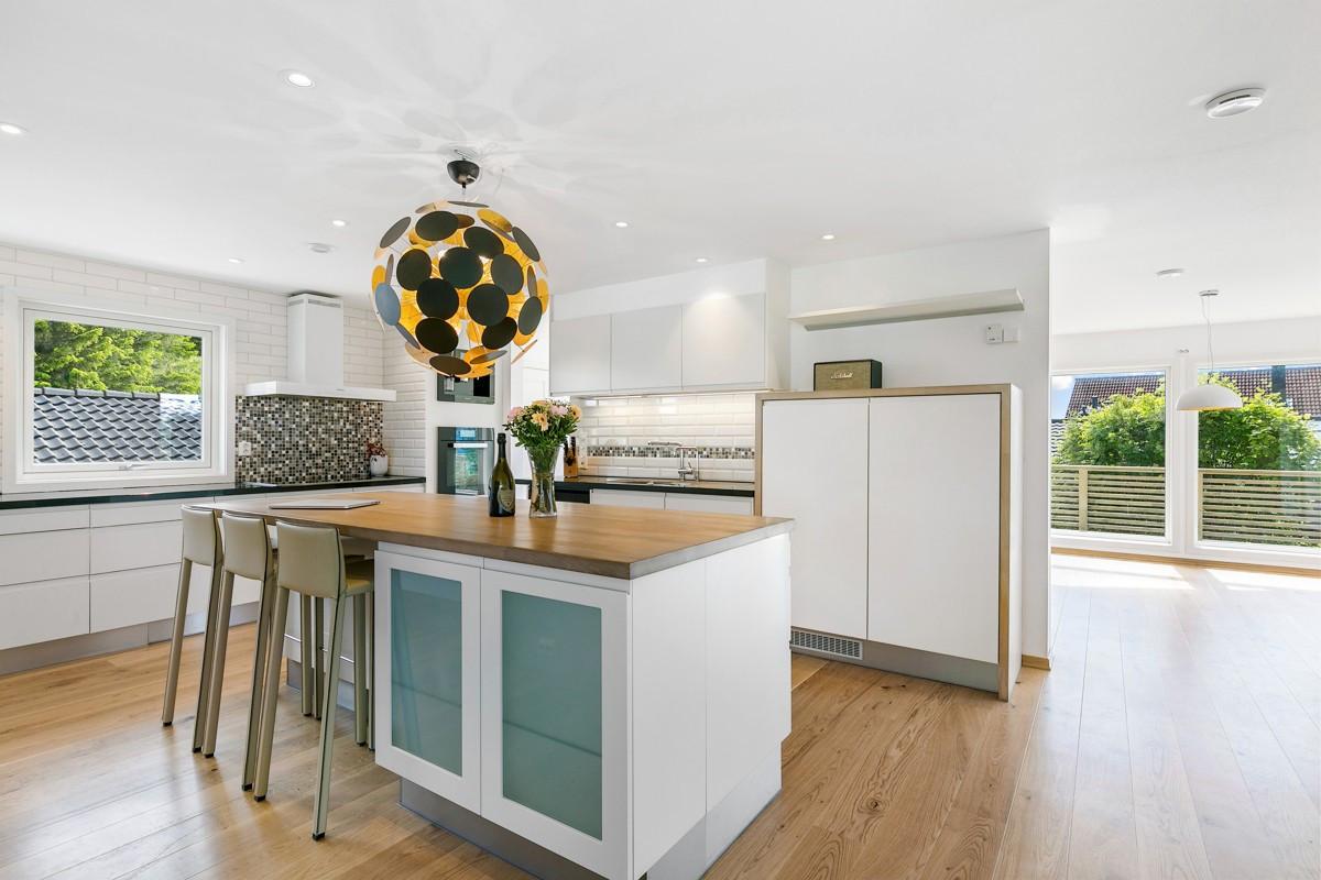 Kjøkken av høy standard med blant annet kjøkkenøy, vinskap, vannkoker i kjøkkenbenk, integrert kaffemaskin mv.