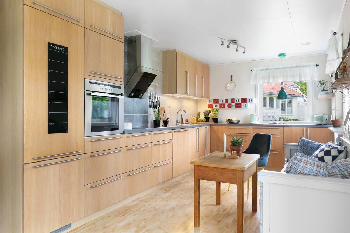 Moderne kjøkken med glatte fronter, fliser over benk og integrerte hvitevarer.