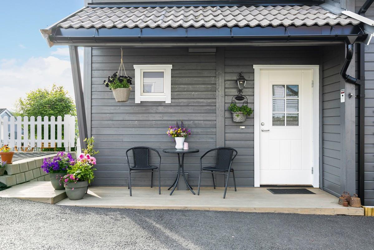 Lekkert inngangspart - med terrassebord rundt hjørnet ned til markterrasse i hage
