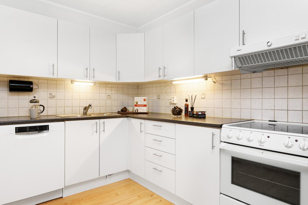 Kjøkken med fliser over benk, samt opplegg for oppvaskmaskin