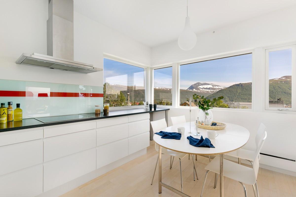 Kjøkkenet fremstår lyst og moderne med glatte hvite fronter og glassplate over benk