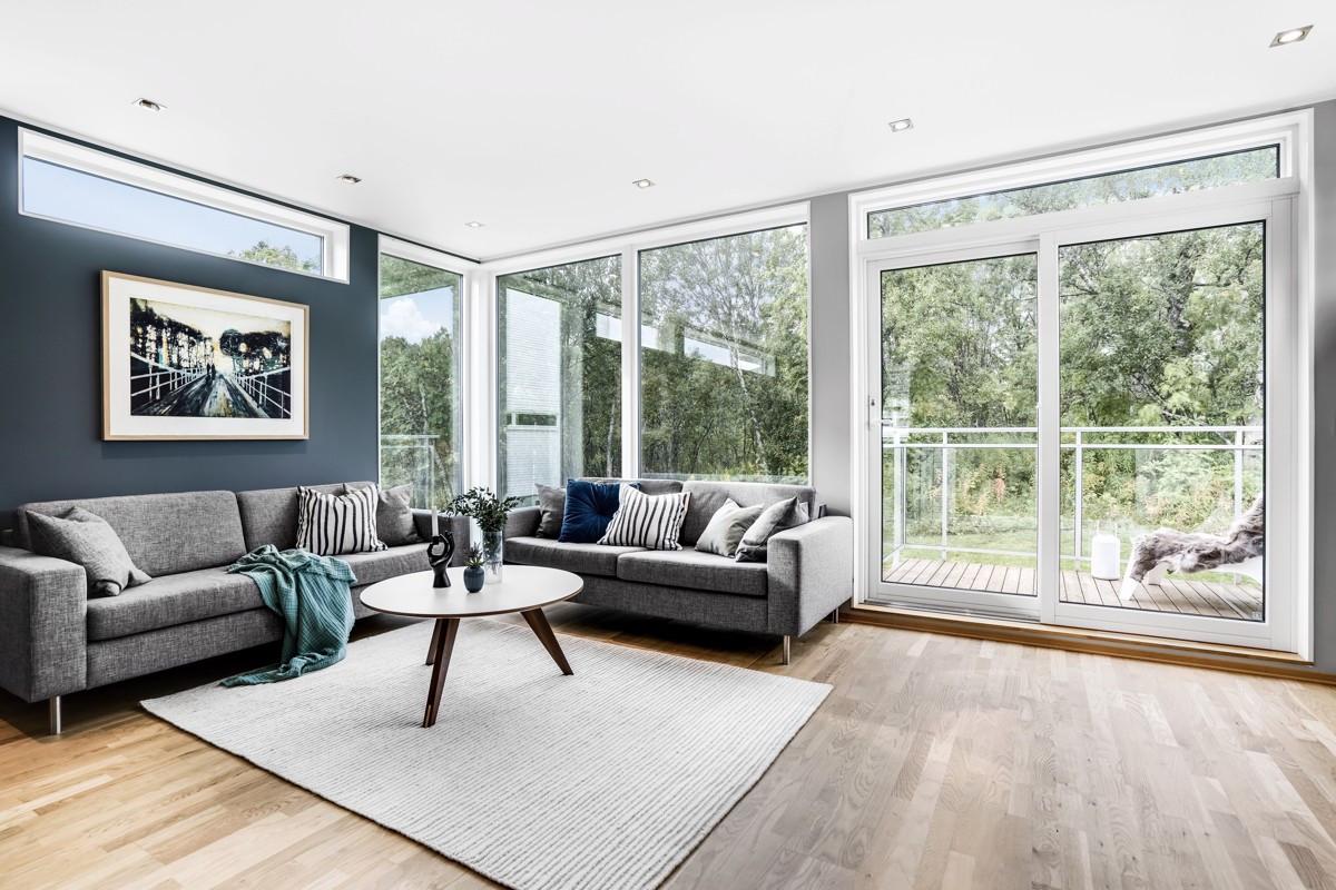 Skjermet stue med store vindusflater og utgang til vestvendt veranda