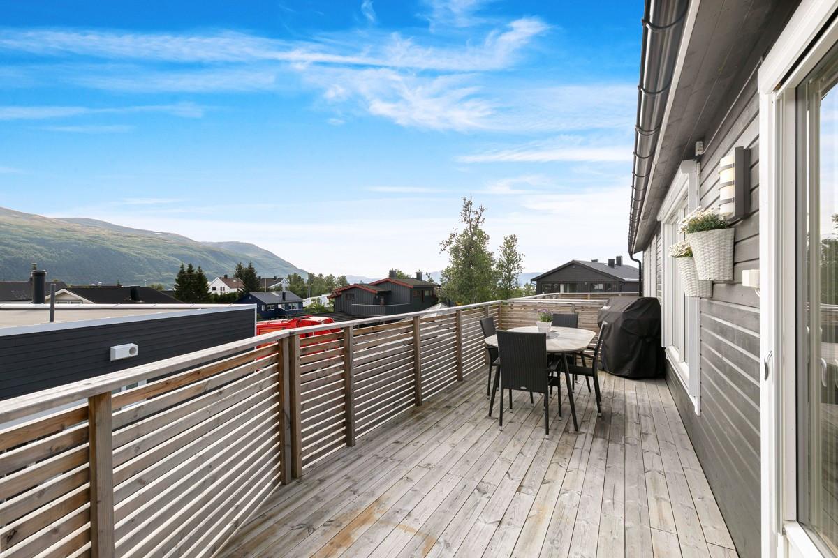Utgang fra stue til stor østvendt veranda med flott utsikt der det er fint å nyte formiddagssola