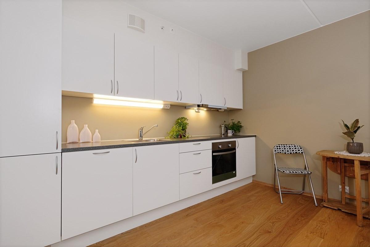 Kjøkkeninnredningen er i hvit utførelse med oppvaskkum i rustfritt stål og ettgreps blandebatteri.