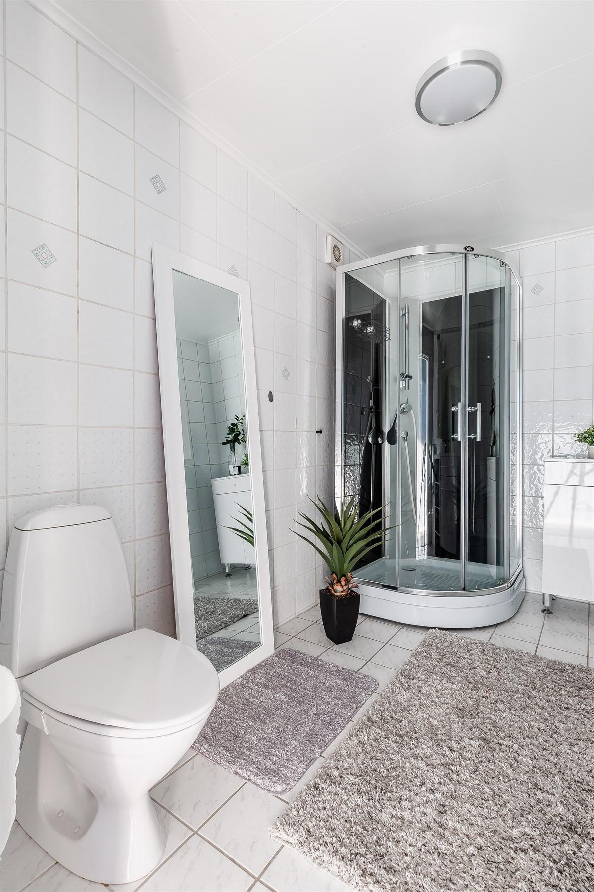 Flislagt baderom med med toalett og dusjkabinett