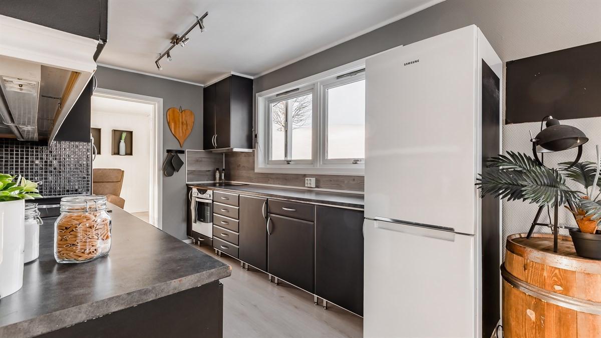 Stort kjøkken med matt sorte overflater, ventilator, lys og strømuttak