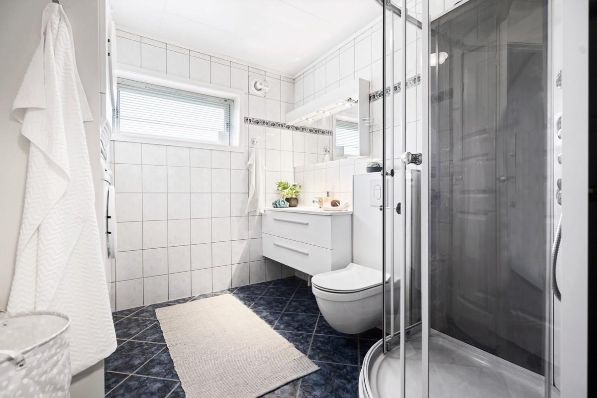 Komplett fliselagt baderom med dusjkabinett, vegghengt toalett og baderomsinnredning