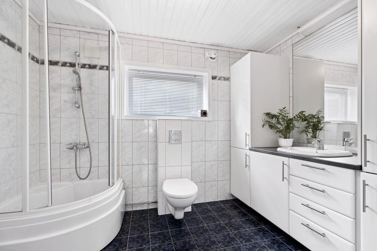 Komplett fliselagt baderom med vegghengt toalett, dusjkabinett og stor baderomsinnredning