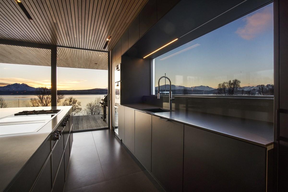 Stort vindu over vask, noe som er med på å skape en luftig og åpen atmosfære