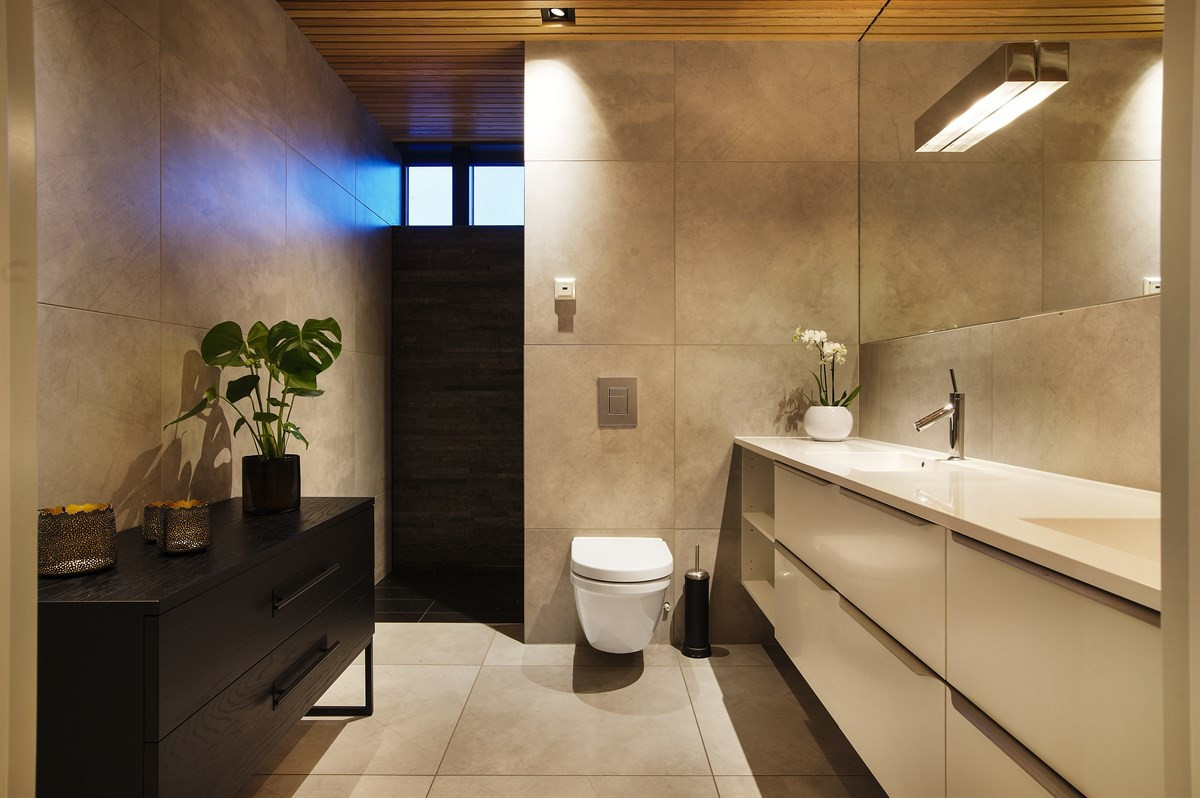 Baderom 1 ligger i 1. etasje med dusjnisje, vegghengt wc og komplett fliselagt