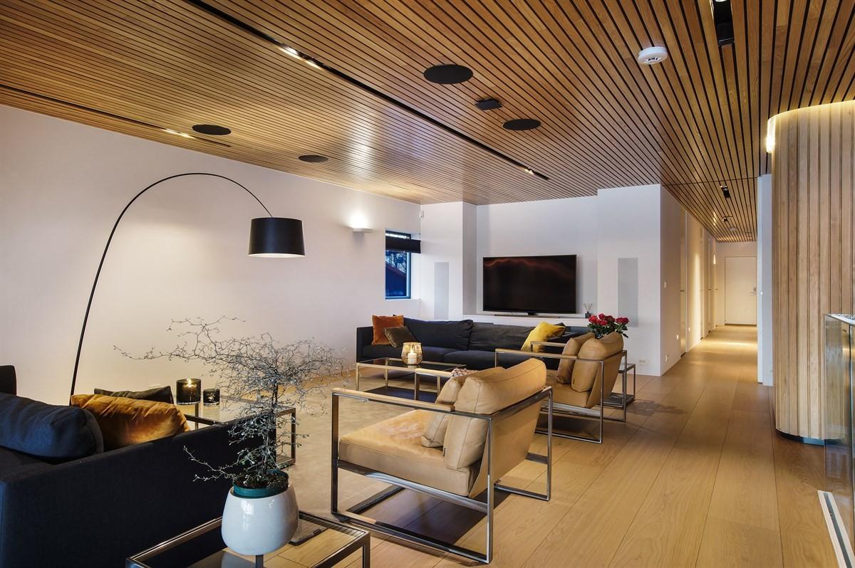 Gulvene i boligen består av eikeparkett, fliser, polert betong og stålslipt betong. Himling med splitpanel av eik
