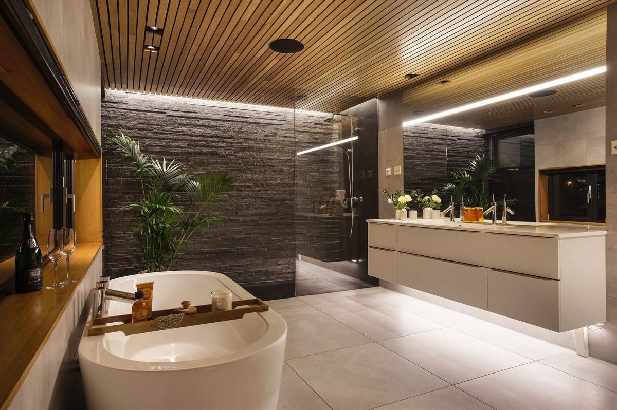 Baderommet inneholder badekar under vindu, dusjnisje og romslig innredning i tidløs utførelse