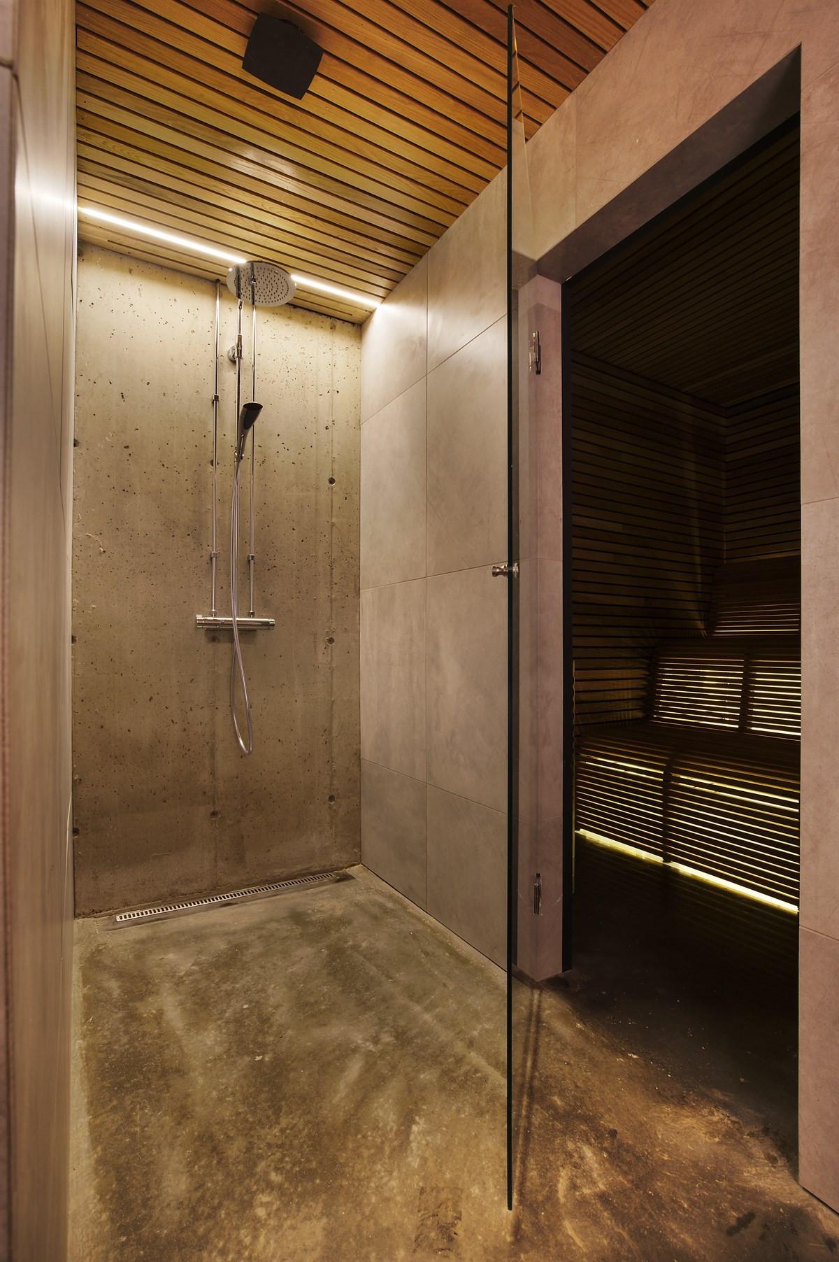 Dusjrom i underetasjen med gulv i polert betong, vegger i betong og fliser