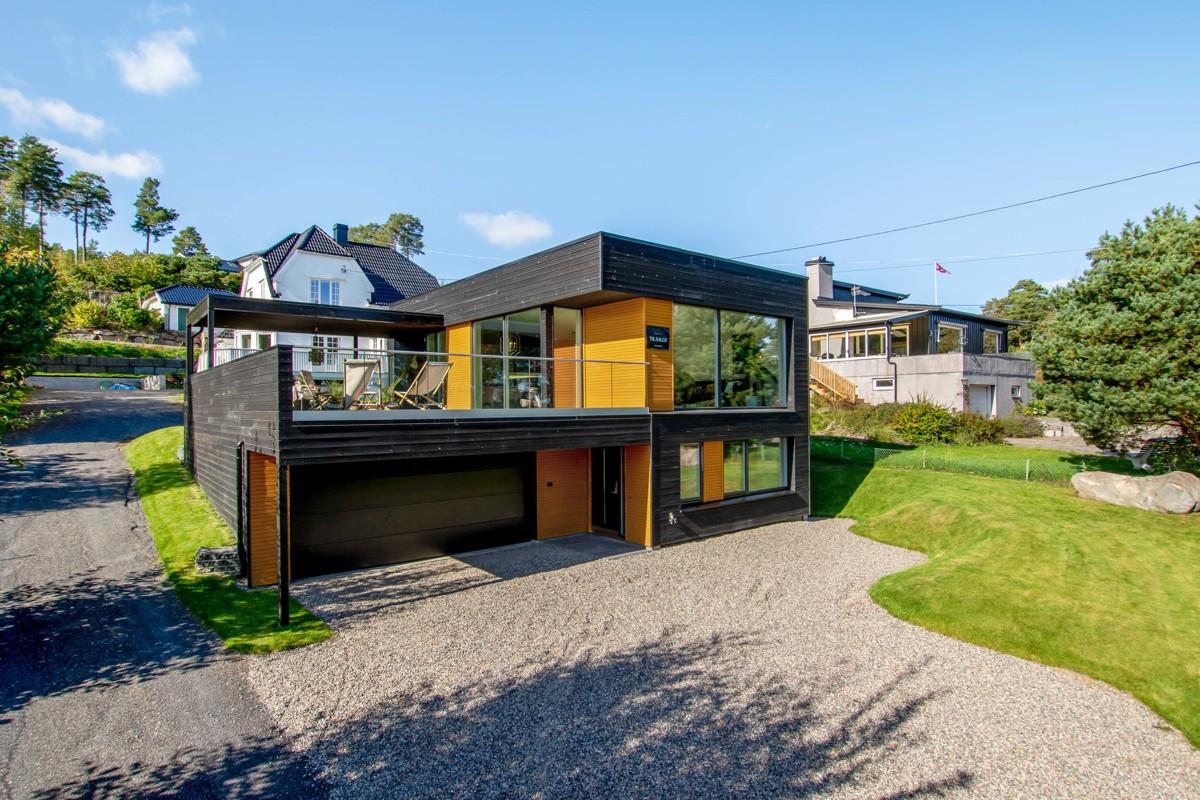 Et steinkast fra sjøen ligger et nybygget, arkitekttegnet funkishus.
