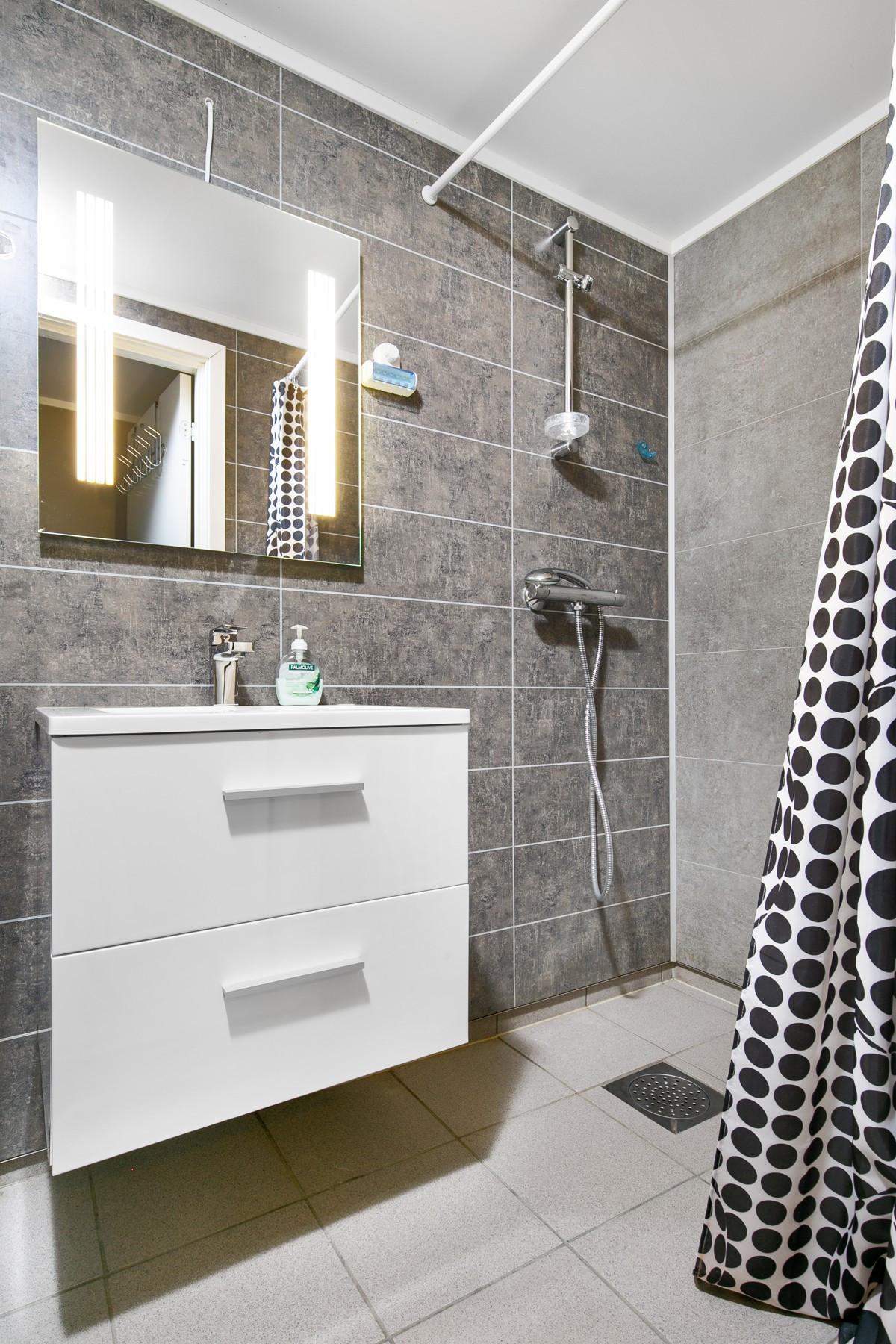 Baderom med baderomsinnredning, dusjnisje og toalett.