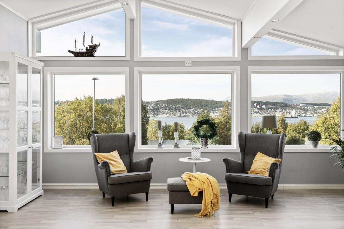 Romslig stue med store vindusflater i hoveddel. Mulighet for flere sittearealer