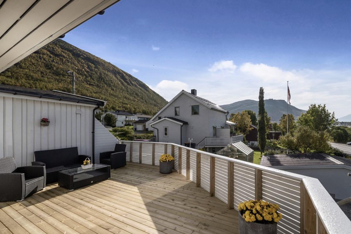 Utgang fra stue til sørvestvendt veranda med utsikt til bla fjellheis og Ishavskaterdral. Her er det sol fra tidlig formiddag til 23 tiden om kvelden