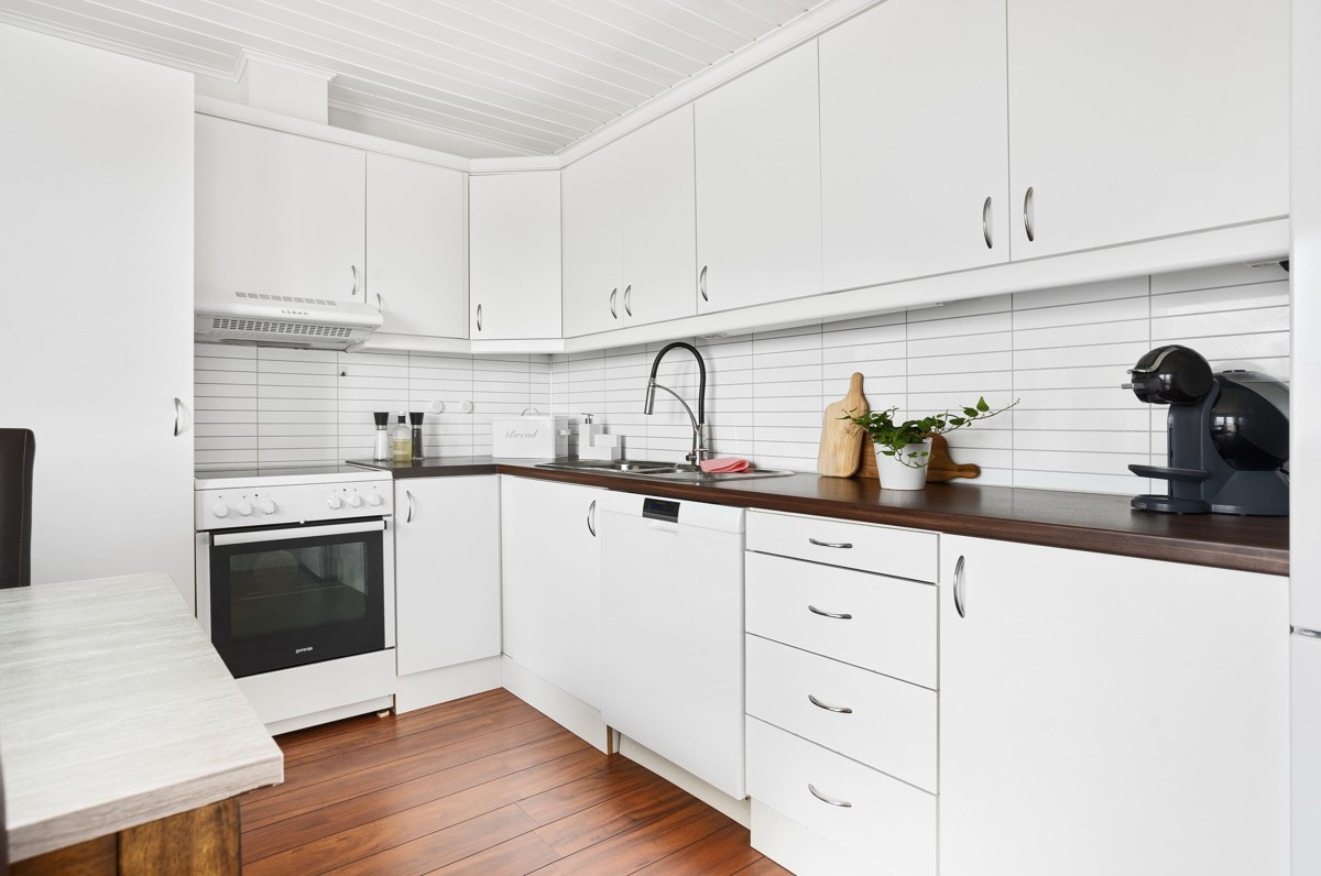 Kjøkken er innredet med tidløse hvite fronter og kitchenboard over benk