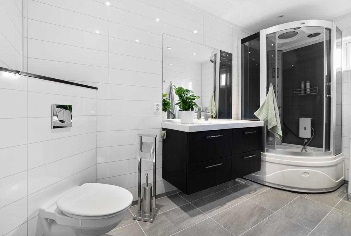 """Moderne og lekkert bad inkluderer dusj med """"waterfall"""" og opplegg for vaskemaskin"""