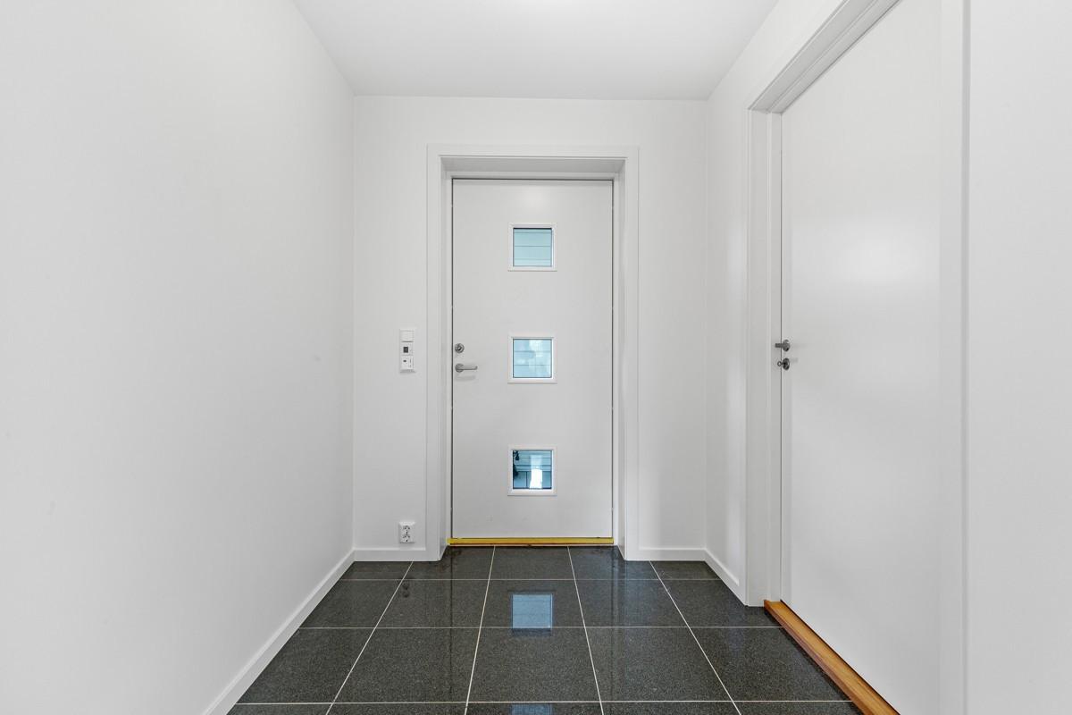 Fliser på gulv i entrè, med bod/teknisk rom inn til høyre
