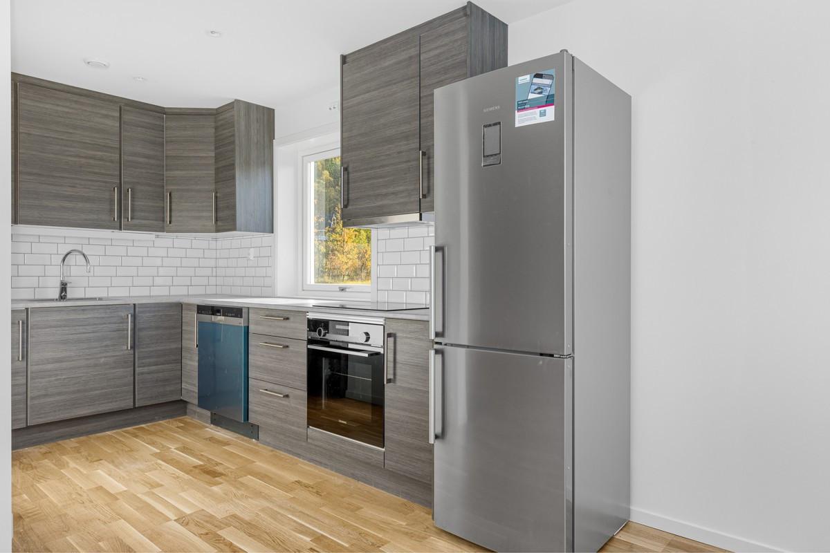 Moderne kjøkken med hvitevarer og fliser over benk