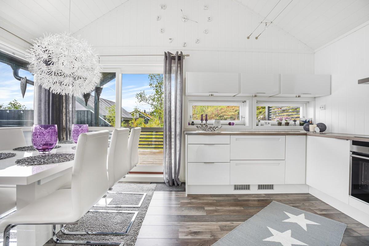 Kjøkkenet har samme gode takhøyde og rommer fint et stort spisebord. Fra Kjøkken er det også utgang til terrassen