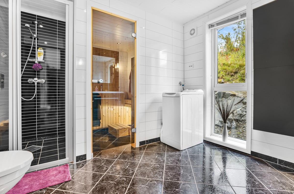 Flislagt bad med veggmontert dusj i nisje og opplegg for vaskemaskin