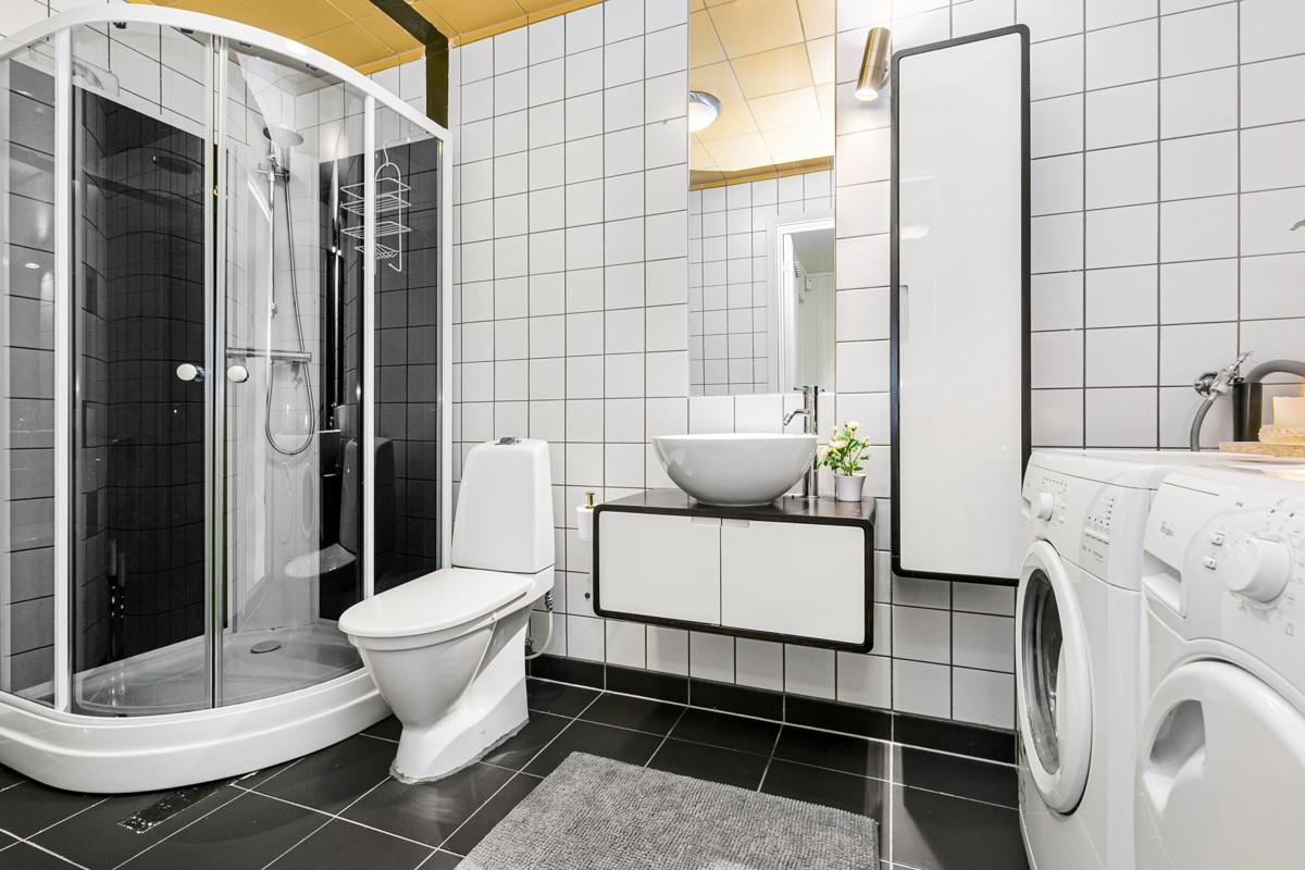 Komplett fliselagt baderom med toalett, dusjkabinett og baderomsinnredning