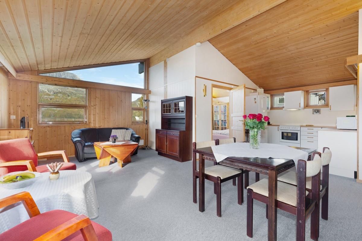 Romslig stue med store vinduer som gir rikelig med lysinnslipp