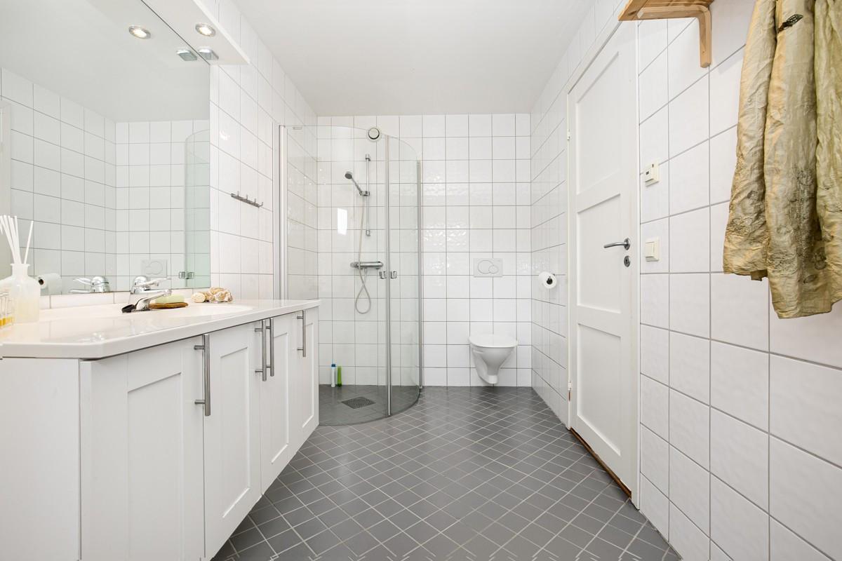 Badet i 2. etasje er fliselagt med dusj, servant og wc