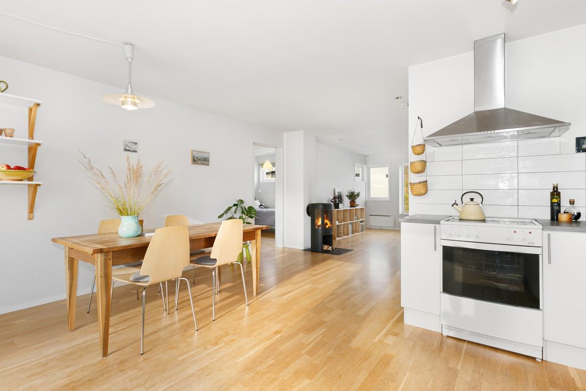 Luftig atmosfære med spisestue og kjøkken i andre enden av stuen