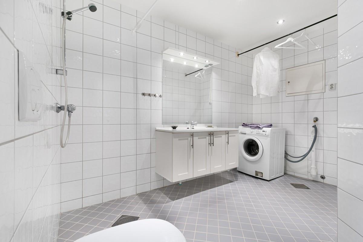 Fliselagt baderom med rom for vask/tørk i 1. etasje