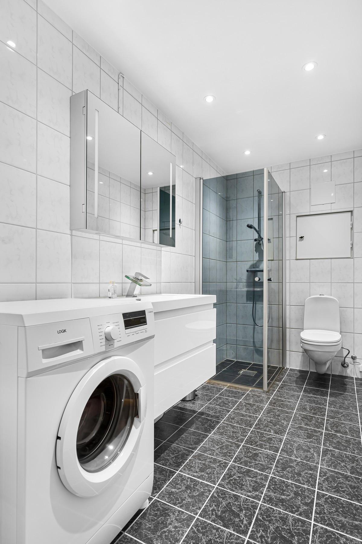 Komplett flislagt bad med opplegg for vaskemaskin, stor dusjnisje, og servant med underskap