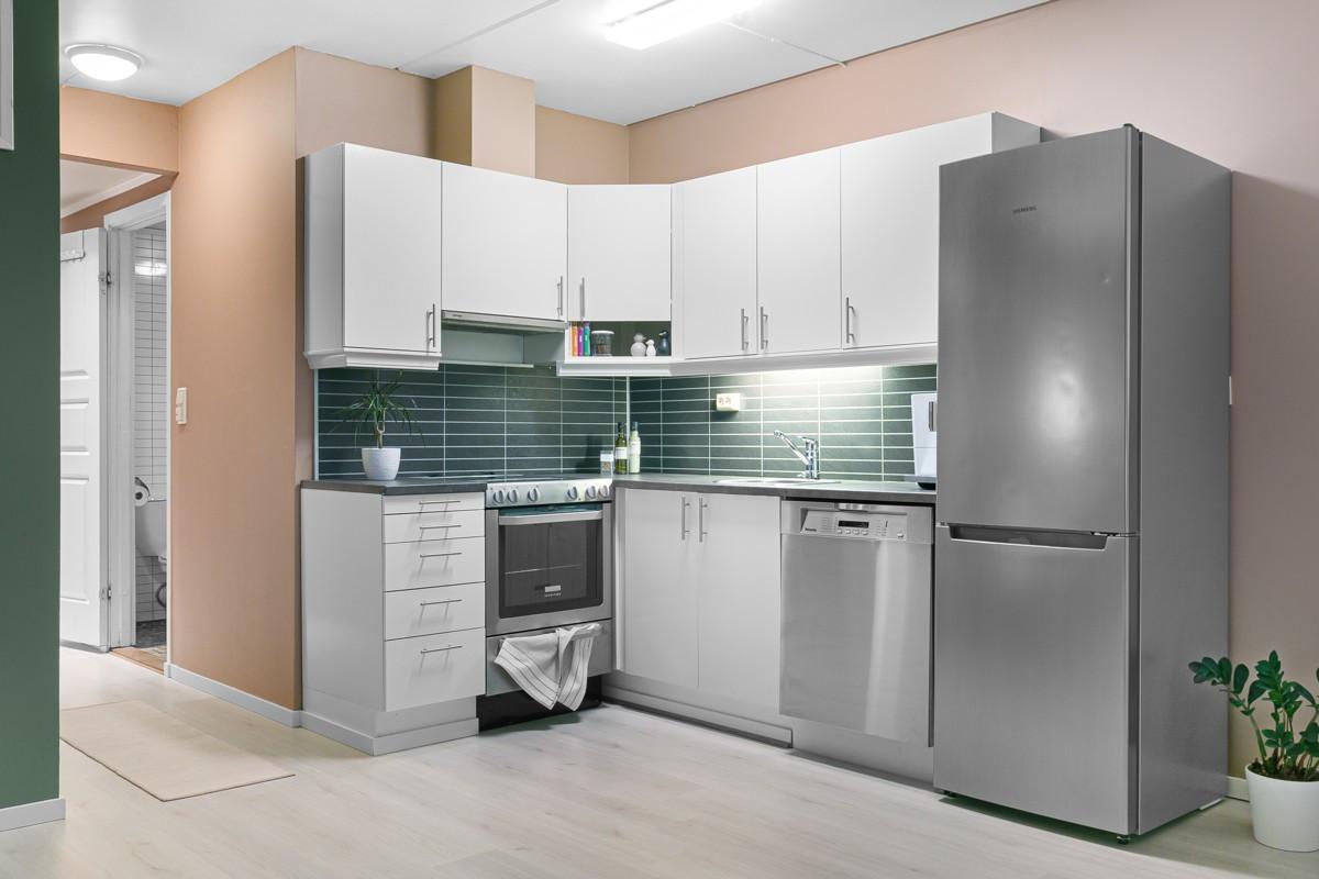 Kjøkken med hvite slette fronter og kitchenboard over benk