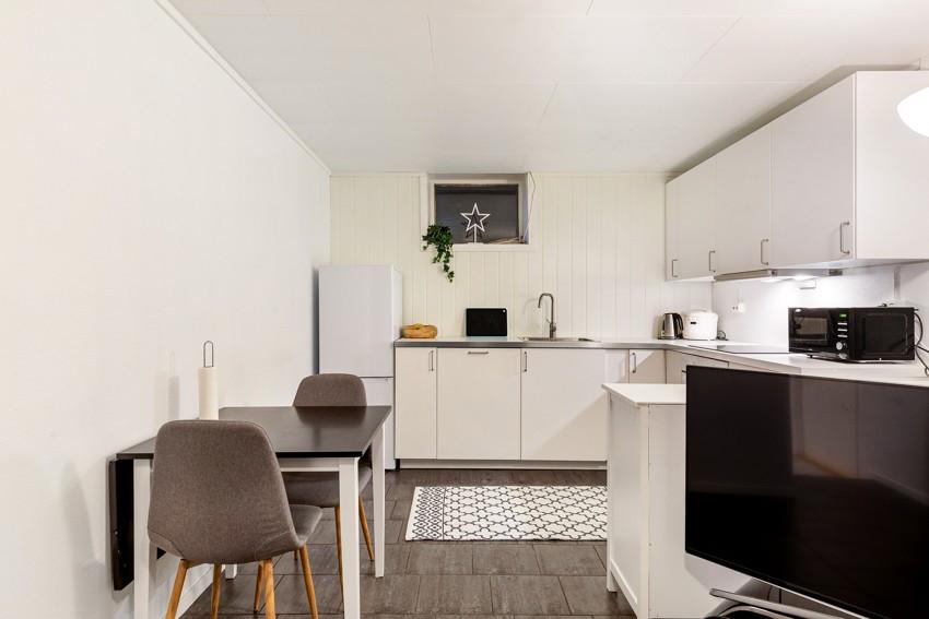 Kjøkken med hvitevarer og gode oppbevaringsmuligheter i over- og underskap