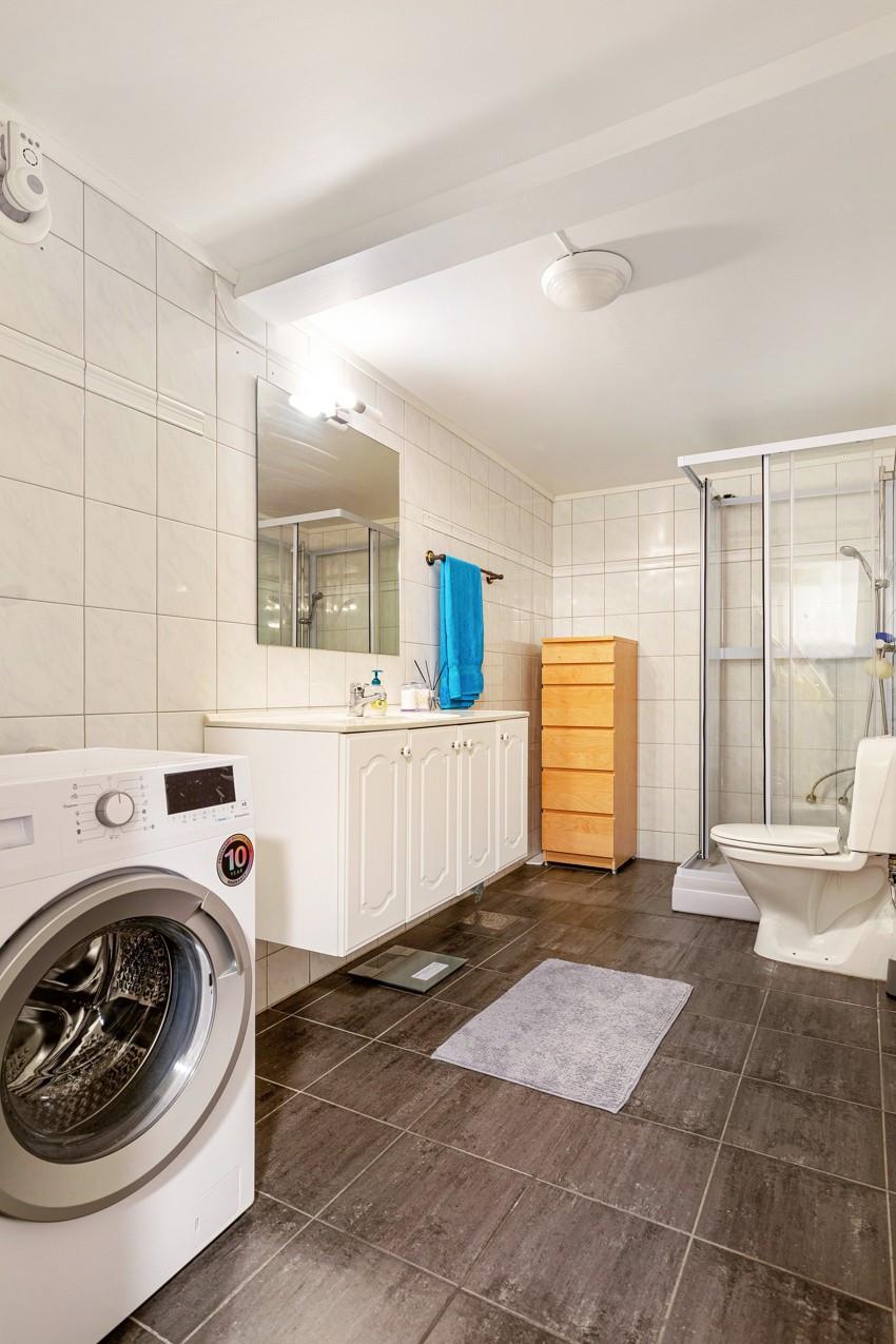 Romselig baderom, med toalett, baderomsinnredning, dusj og opplegg til vaskemaskin