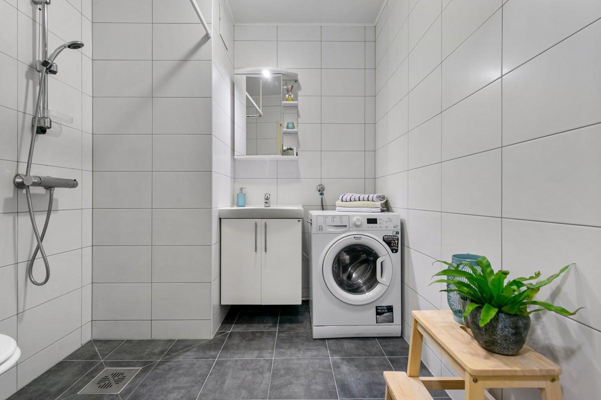 Flislagt baderom med baderomsinnredning, samt opplegg til vaskemaskin