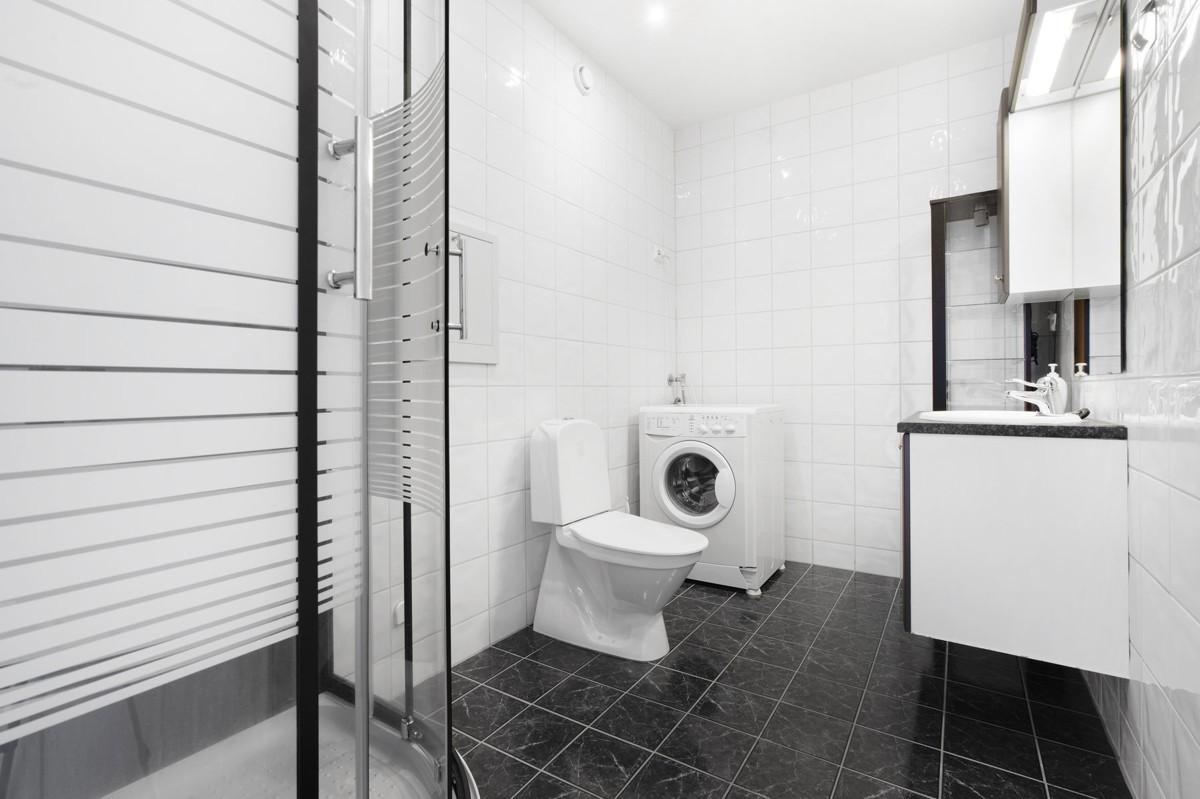 Komplett fliselagt baderom med toalett, baderomsinnredning, dusjkabinett og opplegg til vaskemaskin