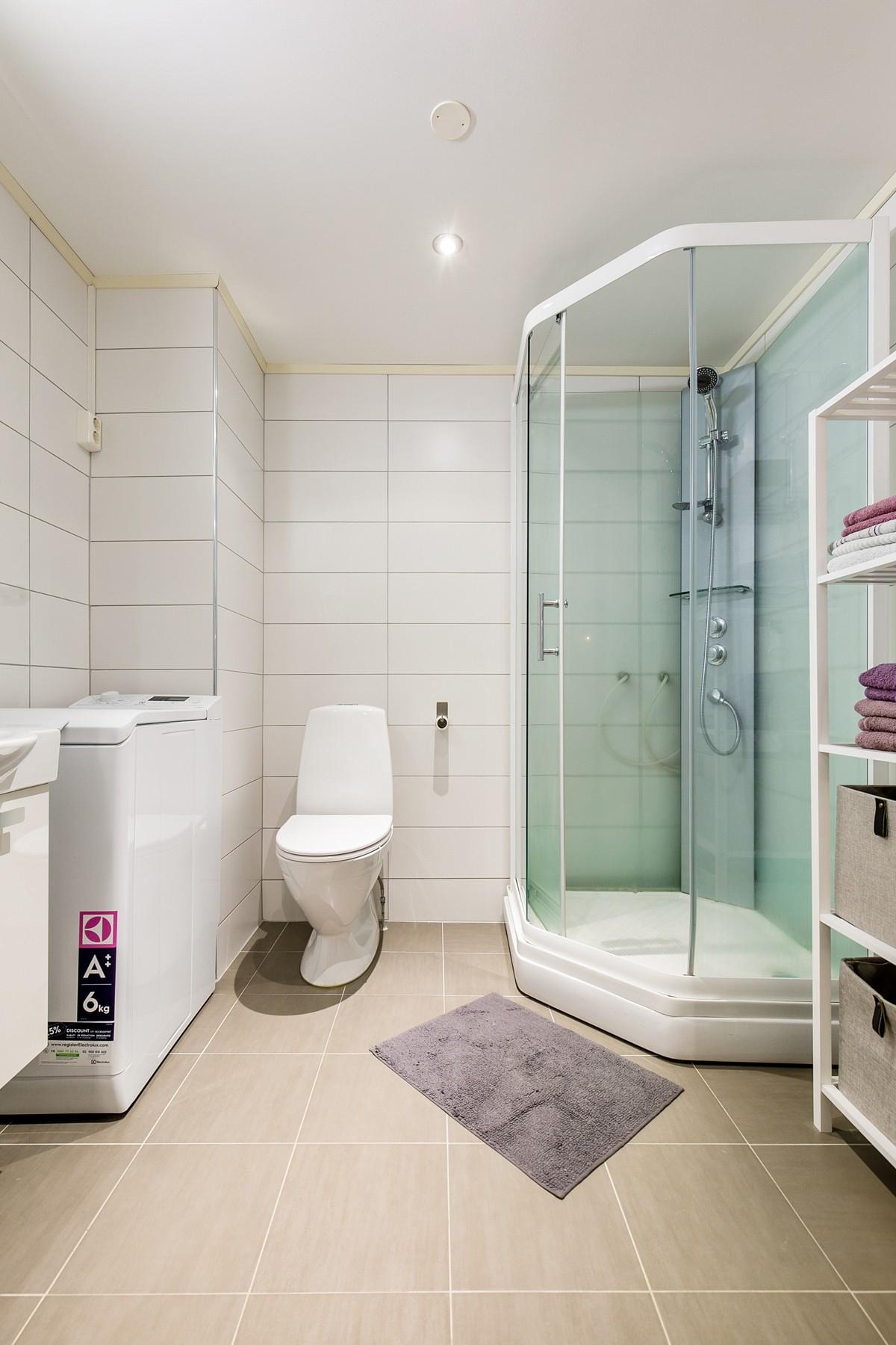 Komplett fliselagt baderom i lyse farger, med dusjkabinett og varme i gulv.