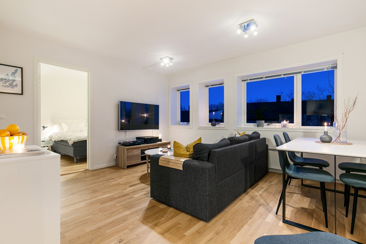 Stilfull stue med store vindusflater som sørger for godt lysinnslipp