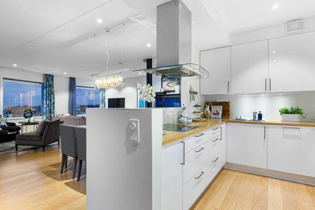 Kjøkkenet er leilighetens midpunkt og er lekkert innredet med kjøkkenøy og praktiske løsninger og godt med lagringsplass