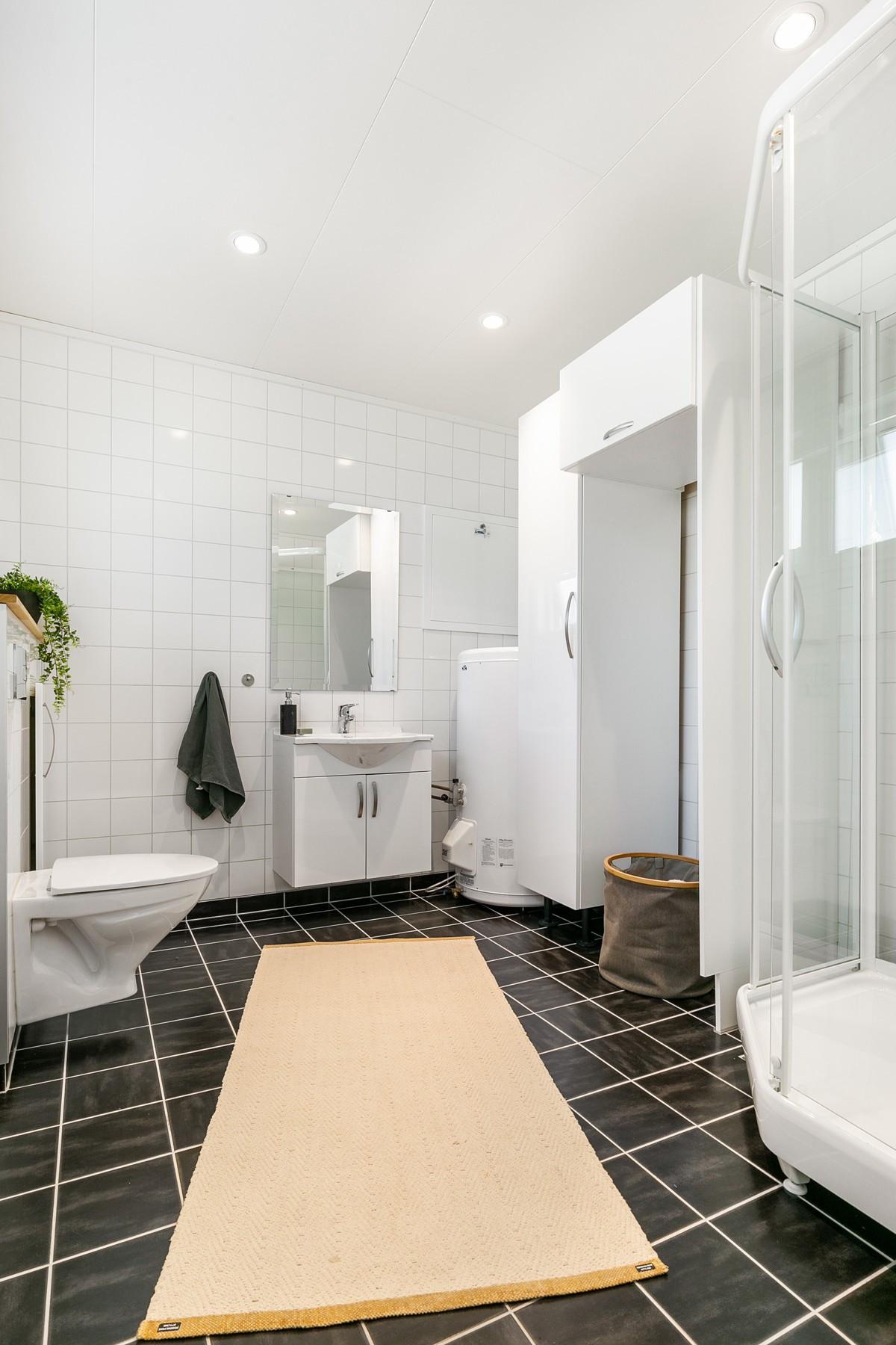 Baderom med liser på gulv, dusjkabinett og rom for vask/tørk