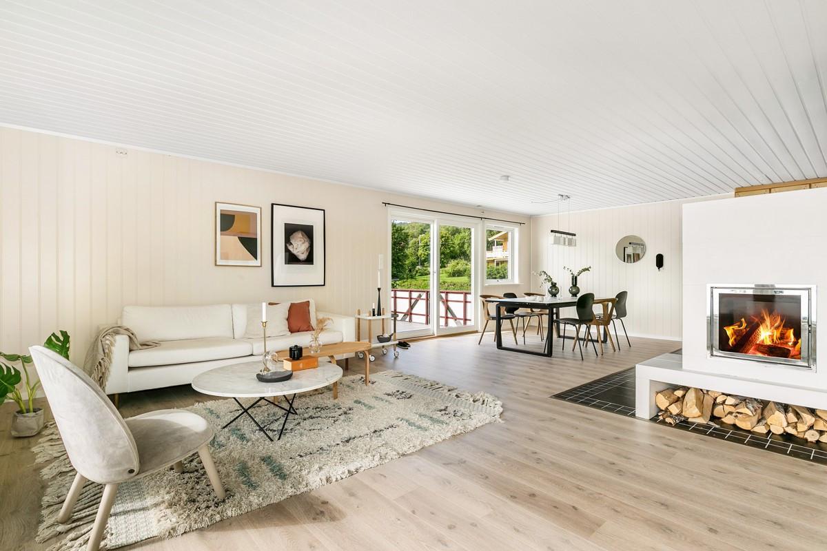 Romslig stue med lyse flater, laminat på gulv og vedovn i stue