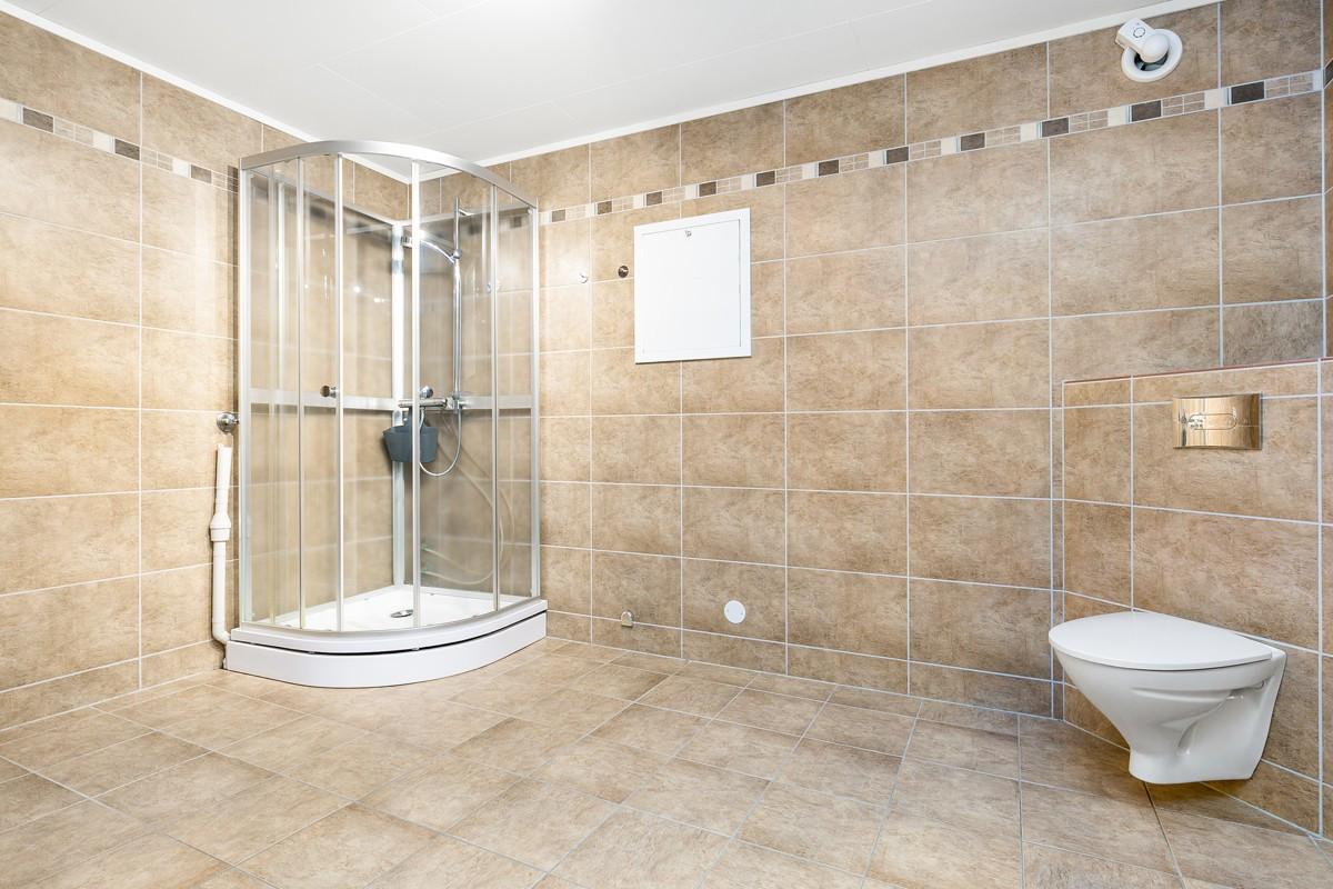 Komplett fliselagt baderom i underetasje med dusjkabinett, wc og servant i 3-roms utleie
