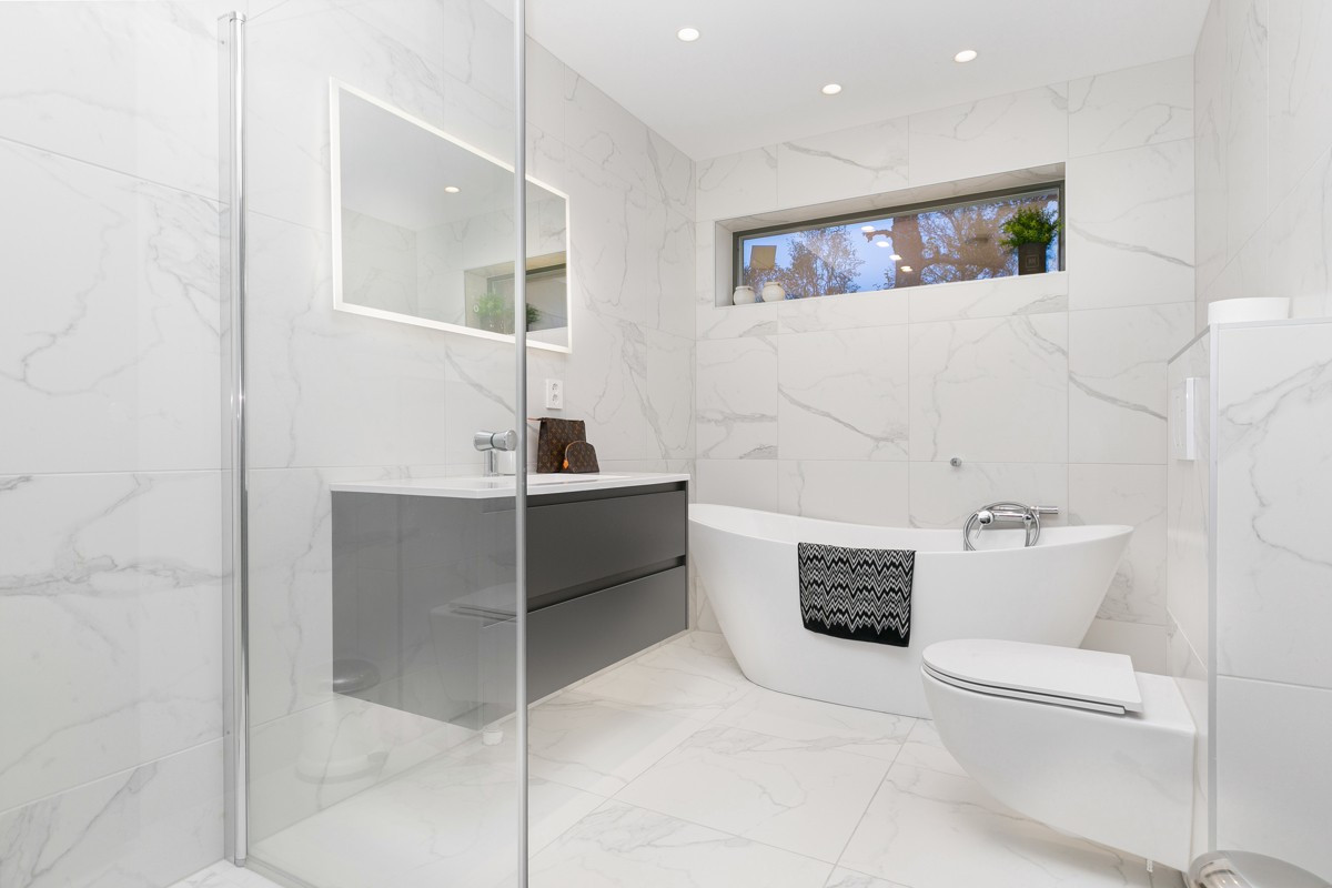 Fliselagt baderom med spotter, gulvvarme, samt både dusj og badekar