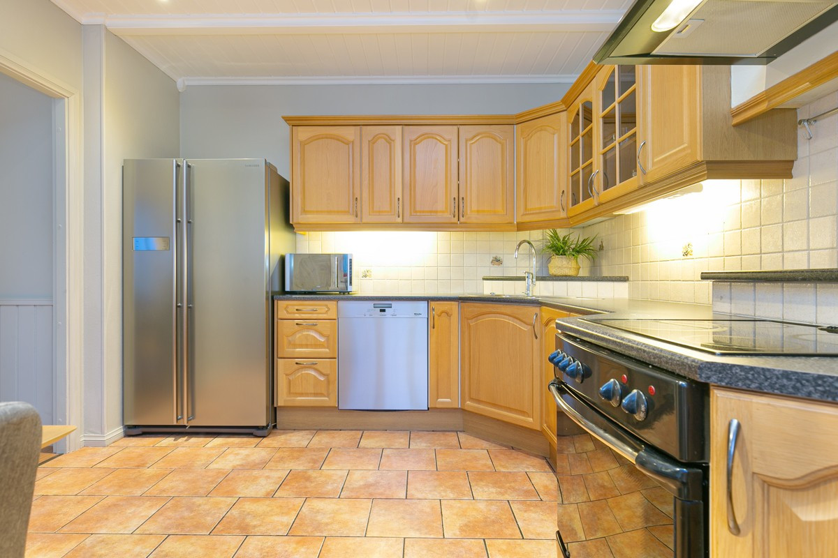 Kjøkkenet er lunt og romslig med profilerte fronter og rikelig med plass til oppbevaring