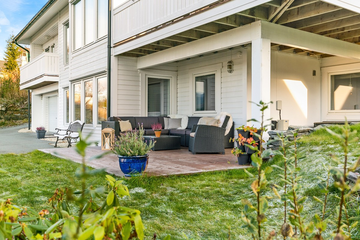 På sommeren er det en lun terrasseplatt med plass til sofagruppe