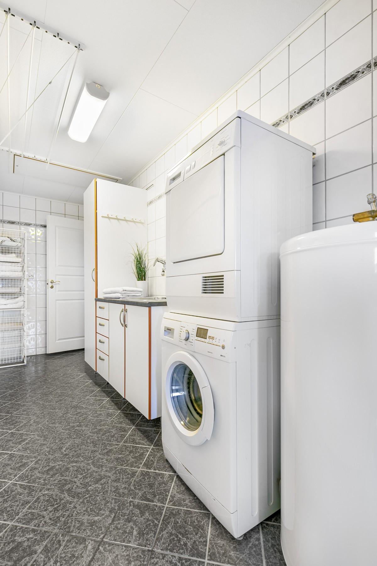 Komplett flislagt vaskerom og god plass til oppbevaring i skap og skuffer