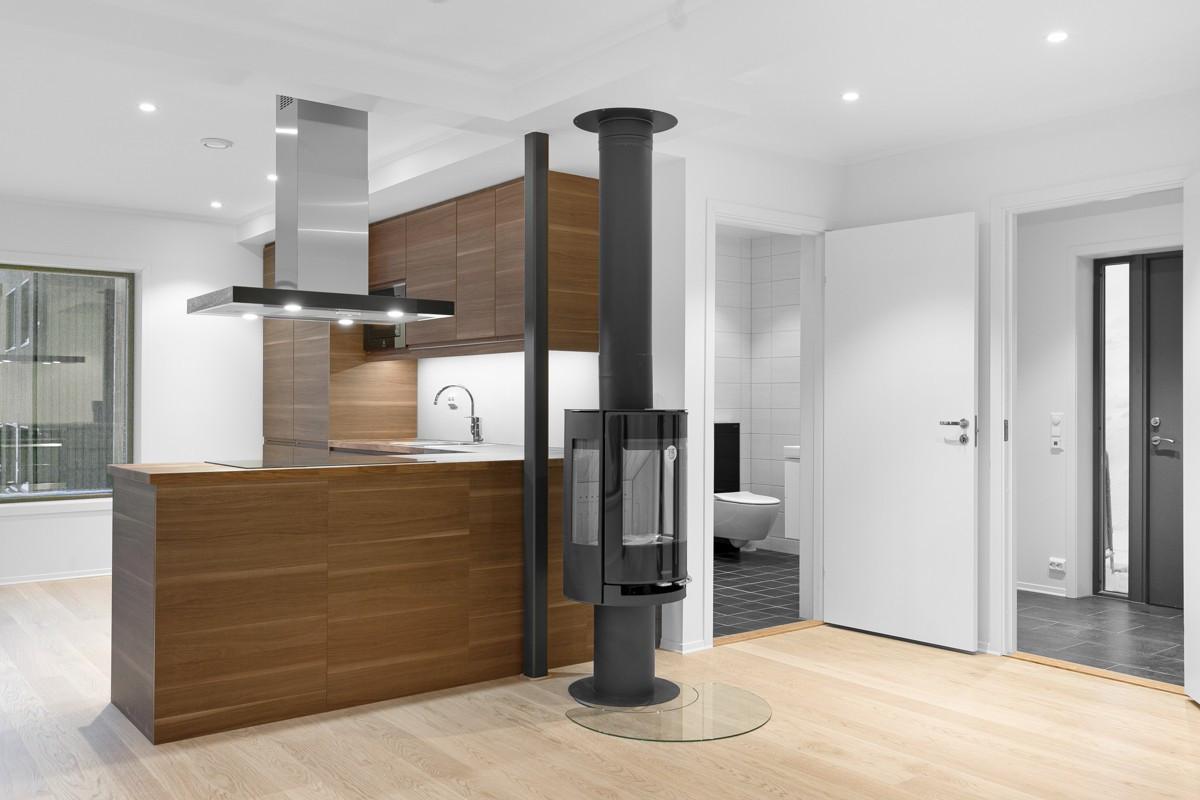I overgang mellom kjøkken og stue er det vedfyr som varmer godt i hele boligen